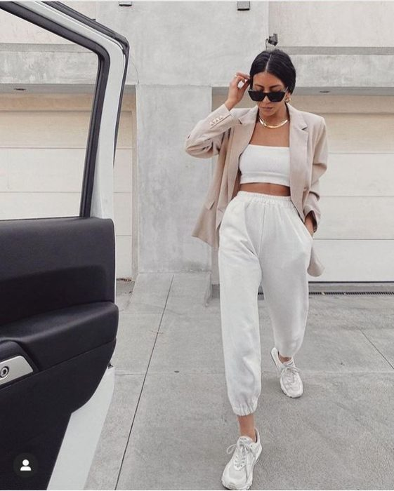 girl wearing sunglasses, white top, beige blazer, white pants and white sports sneakers