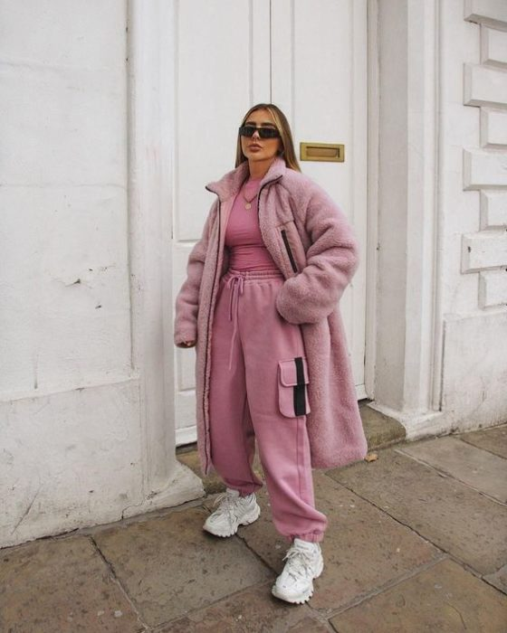blonde girl wearing sunglasses, pink pants, a pink top and pink fur coat, white sneakers