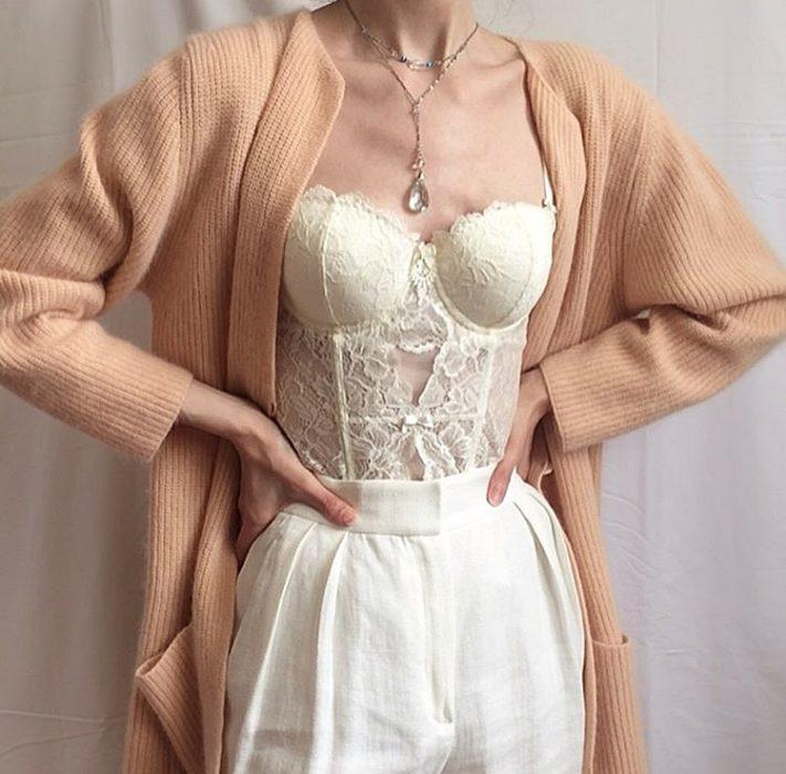 chica usando un bustier color crema con encaje, cardigan color melon, pantalones de vestir blancos y collar