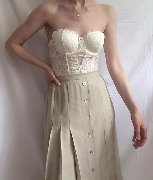 girl wearing white lace bustier with beige buttoned midi skirt