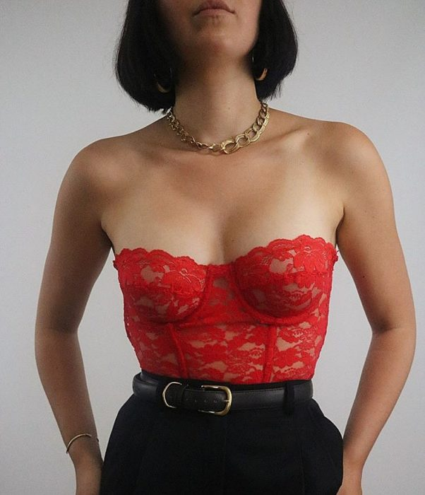 girl wearing a red bustier with lace, black high waist pants with belt and gold necklace