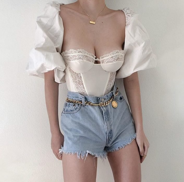 girl wearing white bustier with puffed sleeves, denim shorts and chain belt
