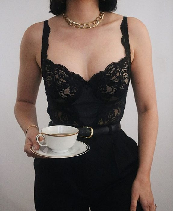 girl wearing black lace bustier, with leather belt, high waist pants and a cup of tea