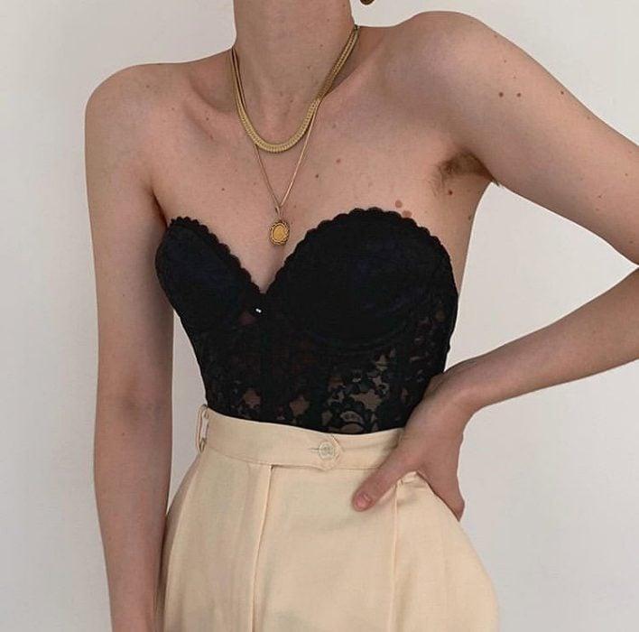 girl wearing black bustier with beige waist dress pants