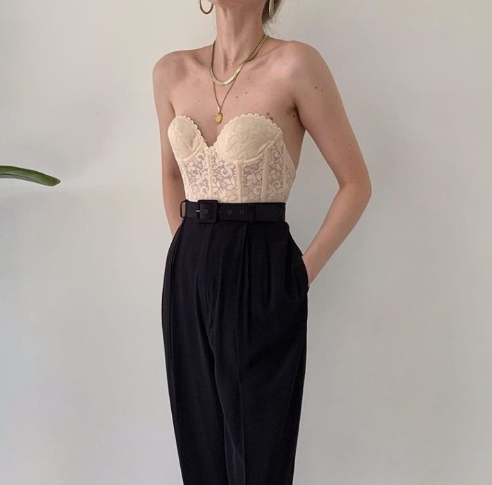 girl wearing beige bustier and black dress pants at the waist