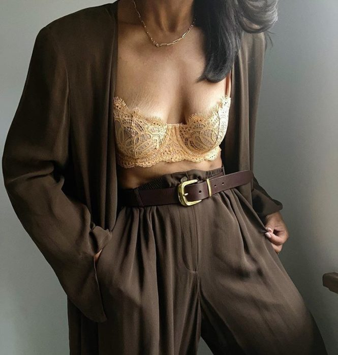 brunette girl wearing a beige bustier with a brown dress suit and black belt