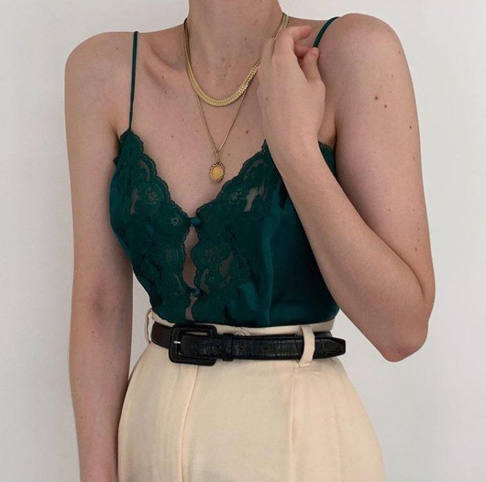 girl with emerald green bustier, beige high waist dress pants