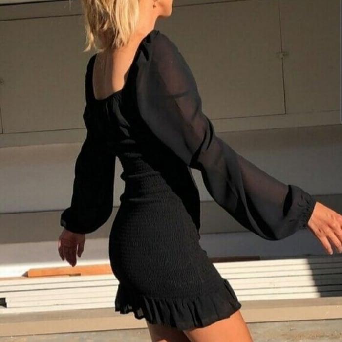 chica rubia con vestido de gaza negro con vuelos y escote cuadrado