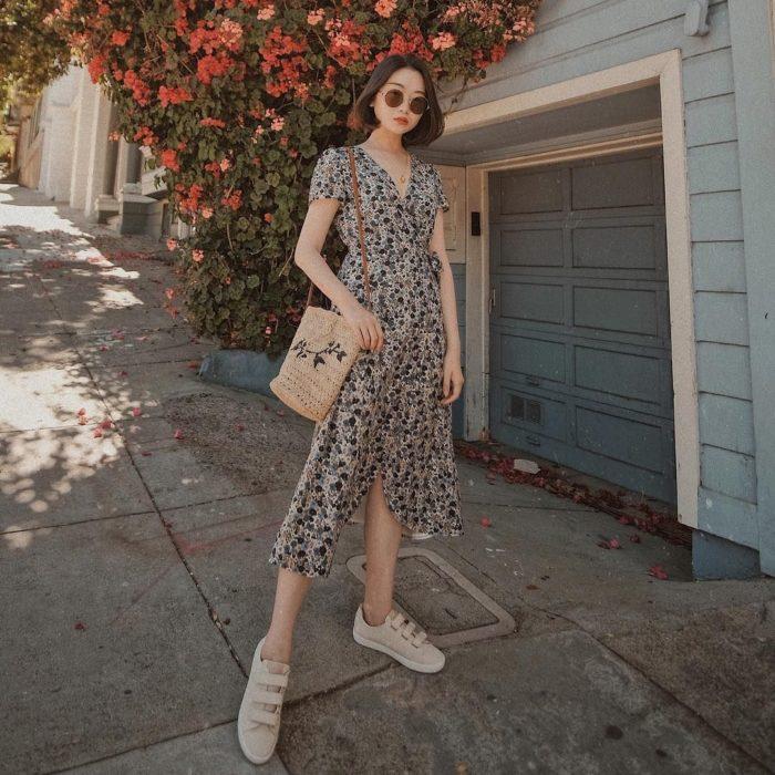 chica con cabello oscuro corto y vestido largo estampado, bolsa tejida beige y zapatos deportivos, lentes de sol