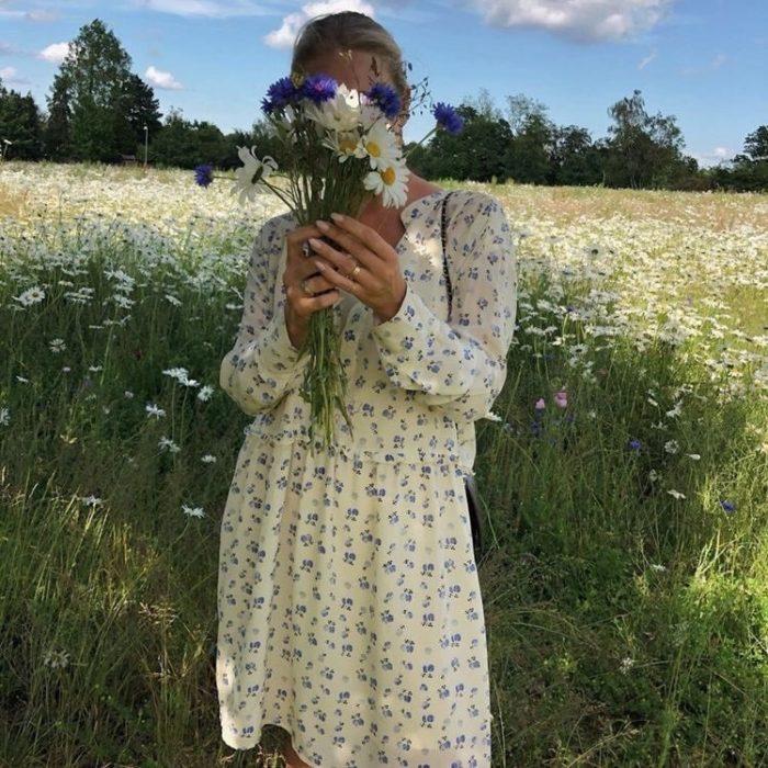 chica rubia posando con flores enfrente de la cara, usando un vestido amarillo pastel con estampado de flores en un campo abierto