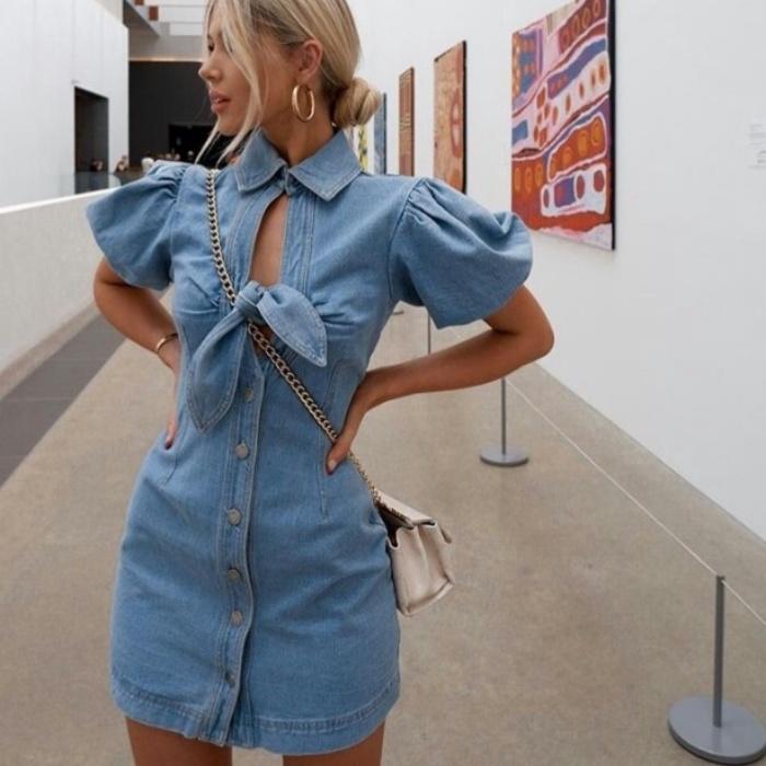 chica rubia usando un vestido de mezclilla denim dress color celeste con un moño en el pecho