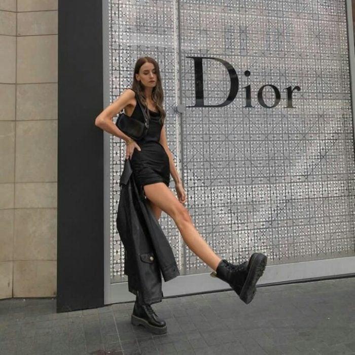 chica de cabello claro con vestido negro, botas de cuero y chaqueta negra de cuero