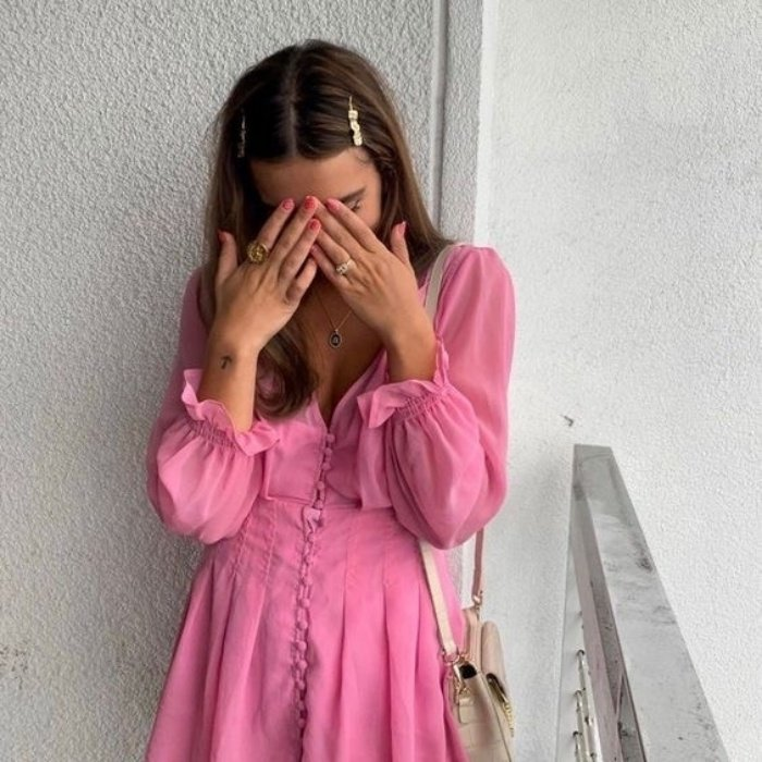 chica con cabello castaño, broches en el cabello y usando un vestido rosa de manga larga con vuelos