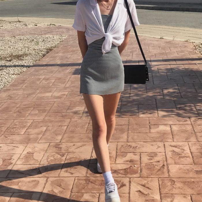 chica con vestido de cuadros blancos y negros, bolsa negra de piel, camisa blanca de manga corta y tenis deportivos blancos