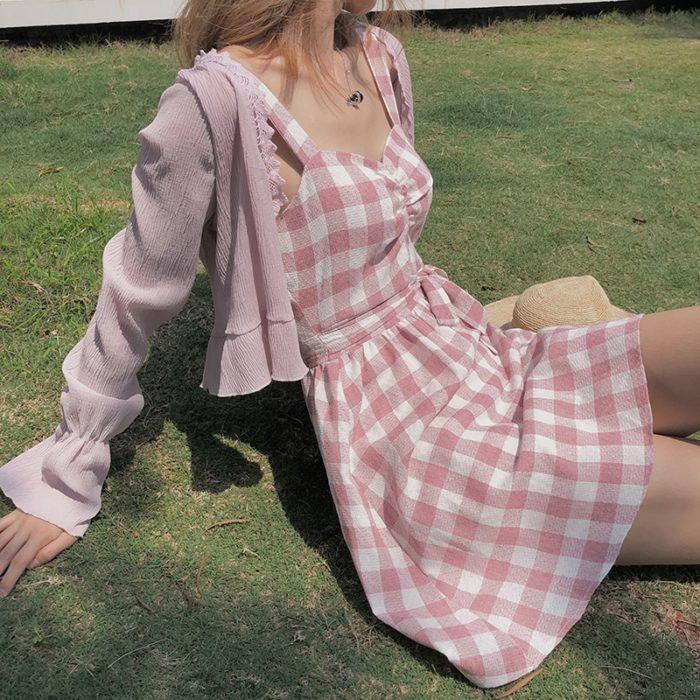 chica con vestido rosa de cuadros blancos y cardigan sueter color rosa pastel