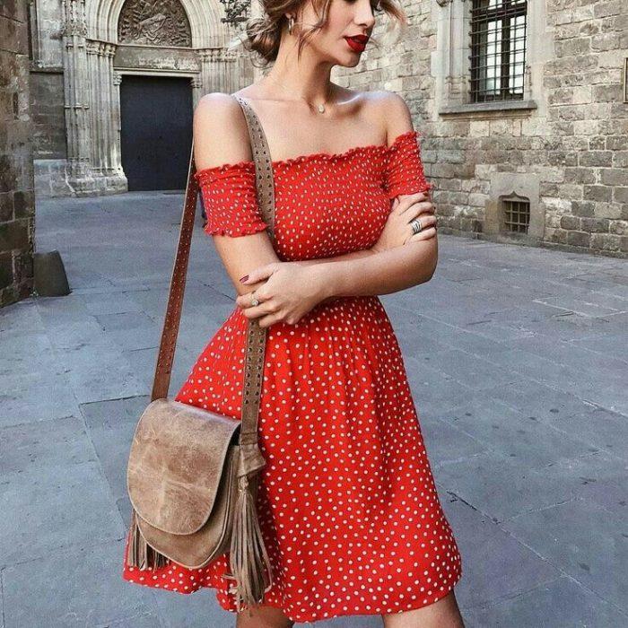 chica con vestido rojo a los hombros caminando por la calle con bolso café de piel