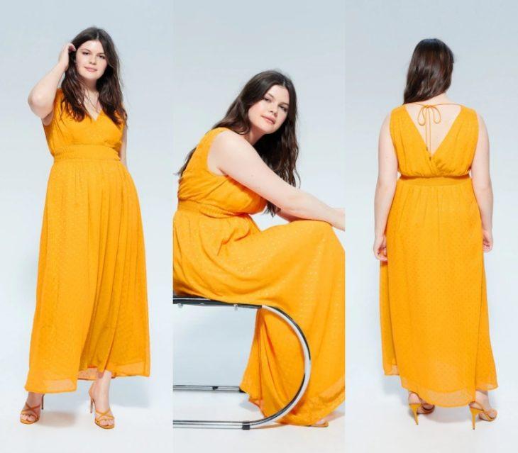 chica curvy con cabello castaño largo, usando un vestido largo amarillo y tacones nude