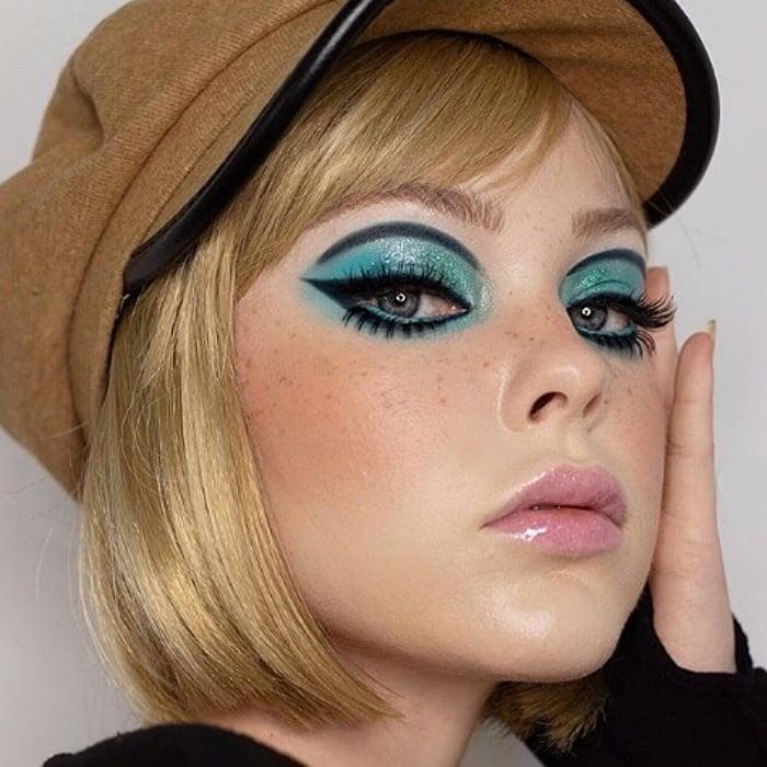 chica rubia con sombra color aqua, delineado de cat-eye negro, gloss transparente, tipo sesentero
