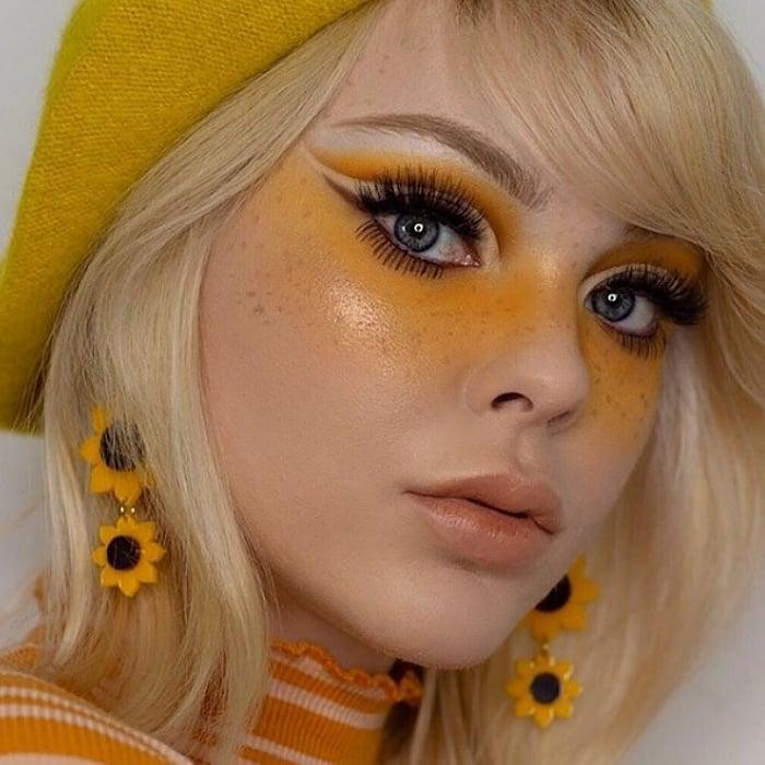 chica rubia usando maquillaje con sombras amarillas, delineado negro oscuro y labios naturales, usando boina amarilla y aretes de girasol