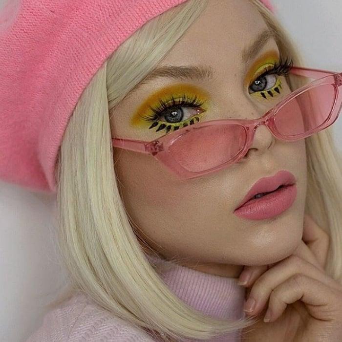chica rubia usando una boina rosa, lentes de sol rosas, maquillaje amarillo con verde, delineado cat-eye negro y labial rosa