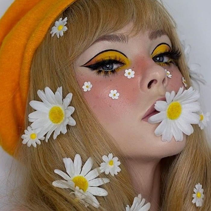 chica rubia de cabello largo usando margaritas flores en el cabello, con maquillaje de sombra de ojos amarilla, delineado negro, blush rosa y boina anaranjada
