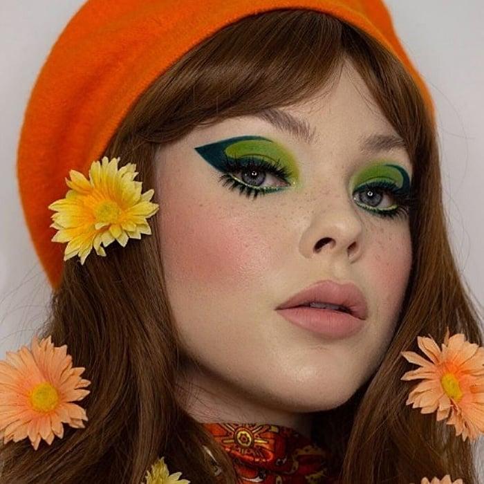 chica con cabello castaño largo usando maquillaje de sombra de ojos verde, delineado oscuro con flores naranjas en el cabello