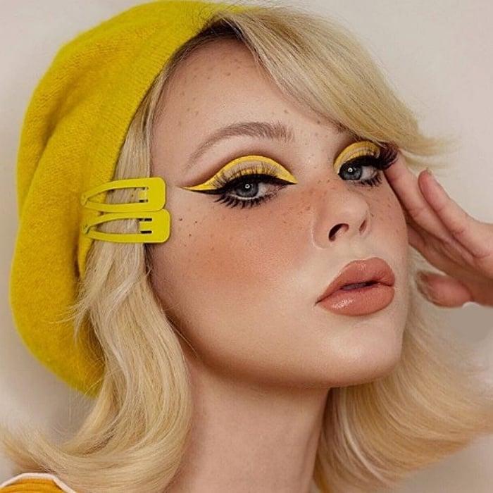 chica rubia con boina amarilla, usando maquillaje color amarillo, delineado tipo cat-eye y lipstick nude con gloss