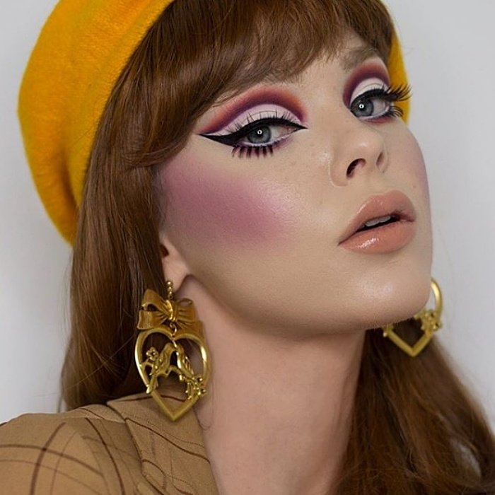 chica de cabello castaño claro usando maquillaje en colores morados, delineado tipo cat-eye, aretes dorados y boina amarilla