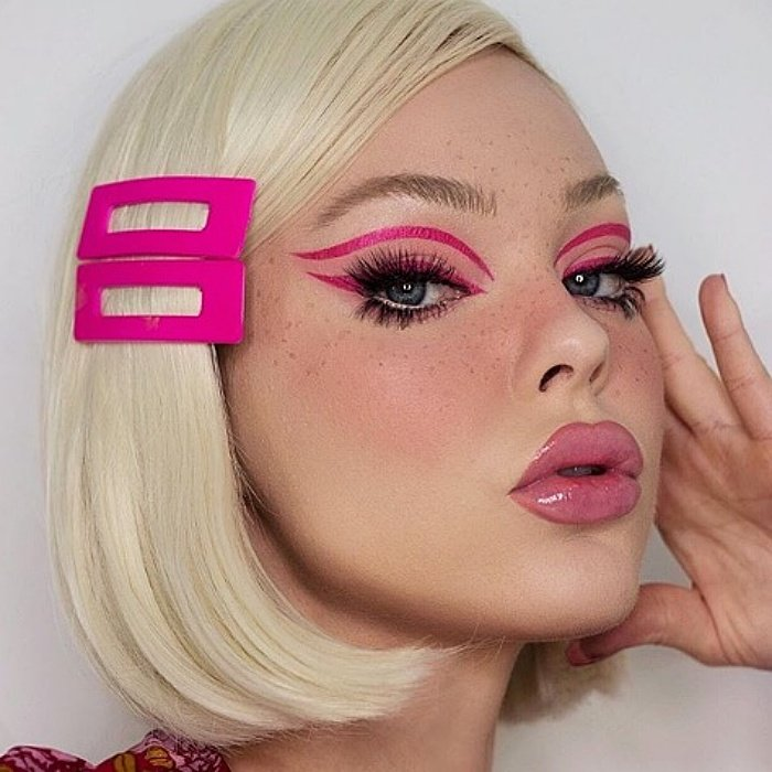 chica rubia usando broches grandes color fucsia, delineado rosa, pestañas postizas y labial rosa con gloss