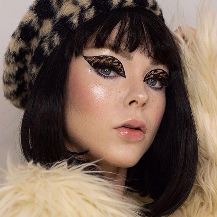 chica de cabello negro corto usando una boina de cuadros negro y beige,