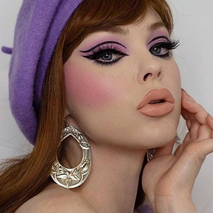 chica de cabello castaño claro con boina morada, usando sombra de ojos rosa, delineado cat-eye negro, lipstick matte nude y aretes grandes de plata