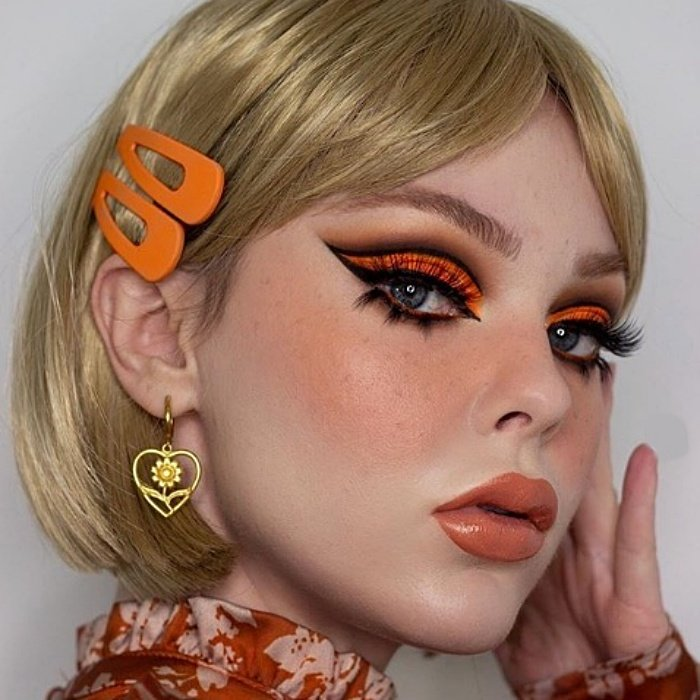 chica rubia con maquillaje sesentero, sombra de ojos color naranja, delineado cat-eye negro, lipstick naranja
