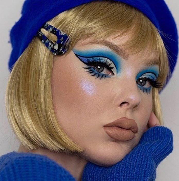 chica rubia con maquillaje monocromático en colores azules, sombra de ojos azul y blanca, delineado sesentero tipo cat-eye y labial nude matte mate