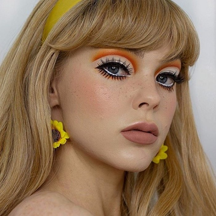 chica con cabello rubio largo, usando maquillaje tipo de los sesentas, delineado con color naranja, pestañas postizas, aretes de girasol