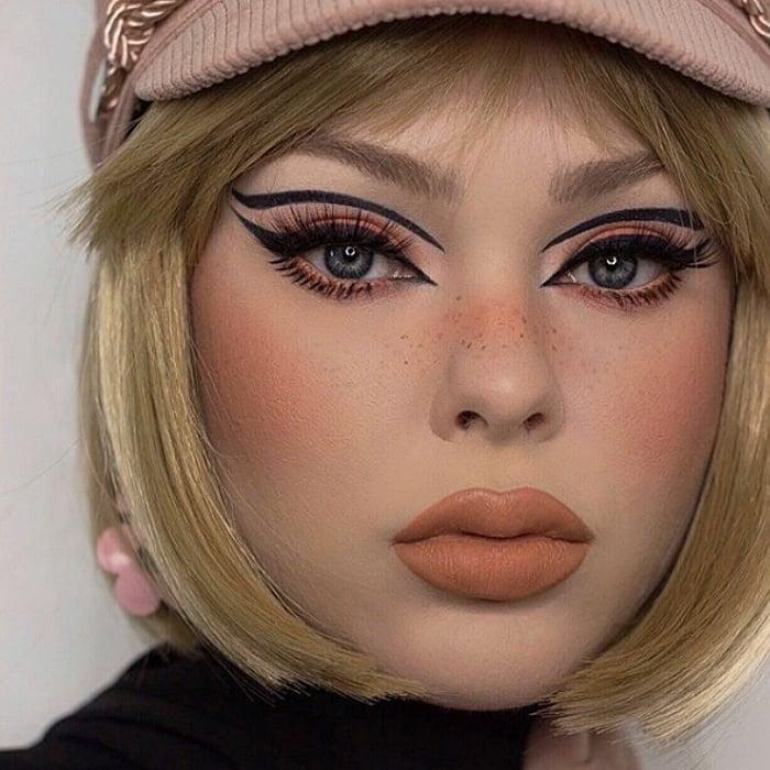 chica rubia con gorra rosa, usando maquillaje de los sesentas con delineado negro tipo cat-eye, labial nude mate y aretes rosas