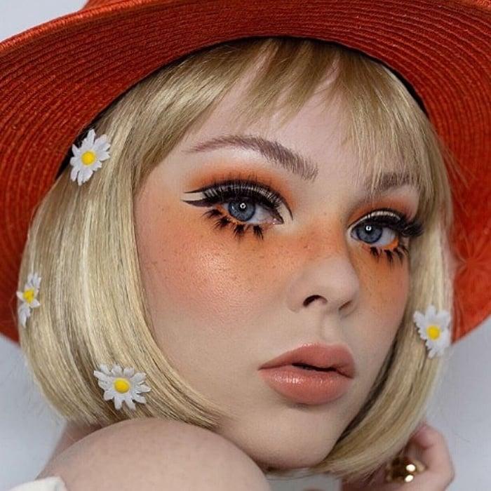 chica rubia usando un sombrero naranja con maquillaje en colores anaranjados