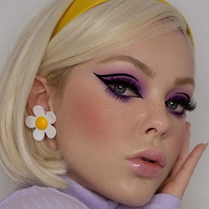 chica rubia con aretes de margarita, sombra de ojos color lila, delineado negro tipo cat-eye y diadema amarilla