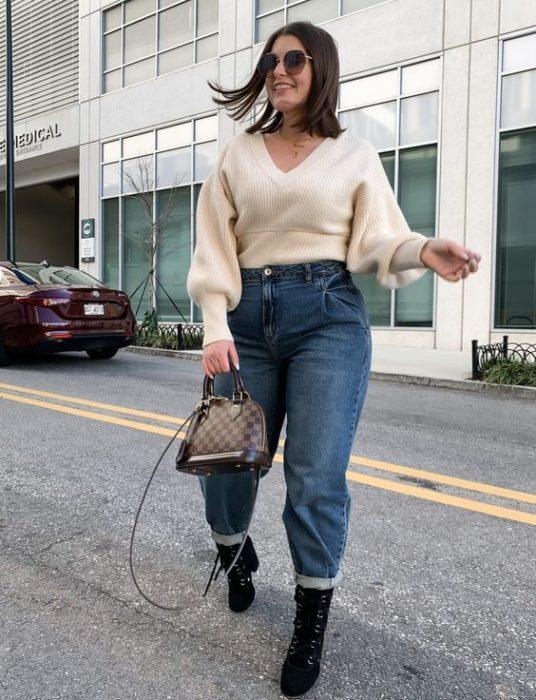 chica de cabello castaño corto usando lentes de sol, con jeans slouchy de mezclilla, suéter beige, botas negras y bolso de piel