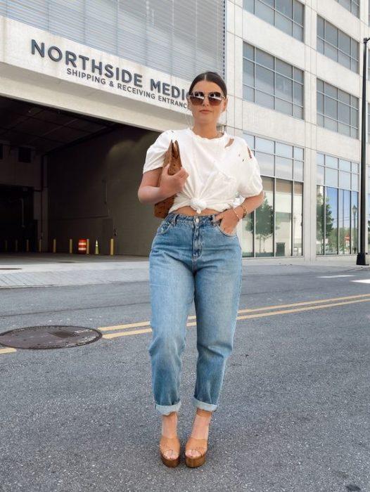 chica de cabello castaño con playera blanca, bolso de mano, jeans slouchy y tacones de piel beige