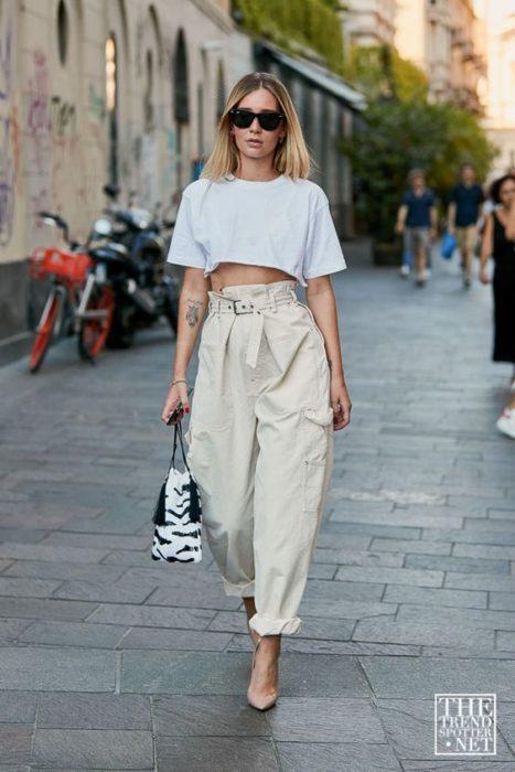 chica rubia con lentes de sol, crop top blanco, jeans slouchy paperbag, bolsa de mano y tacones nude