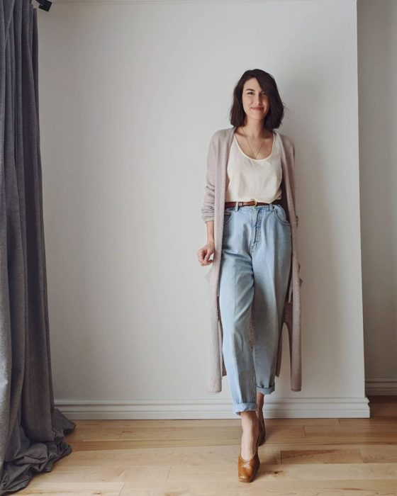chica de cabello castaño usando un top blanco, cárdigan beige oversized, jeans slouchy y flats