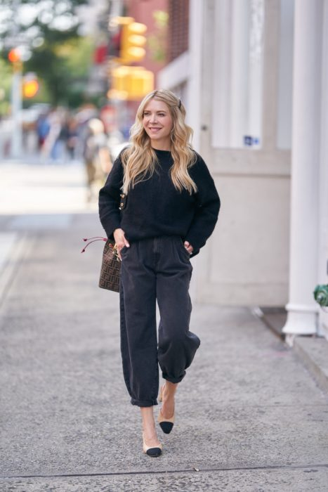 chica rubia con sueter negro, jeans slouchy negros y flats