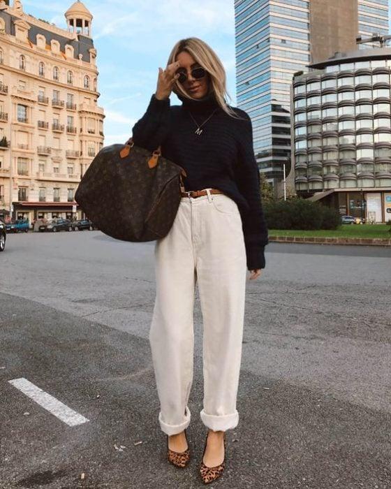 chica rubia con lentes de sol, suéter negro, bolso oversized y pantalones slouchy color crema