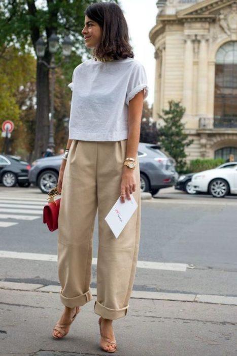chica de cabello castaño con playera blanca, bolso negro y pantalones slouchy color beige