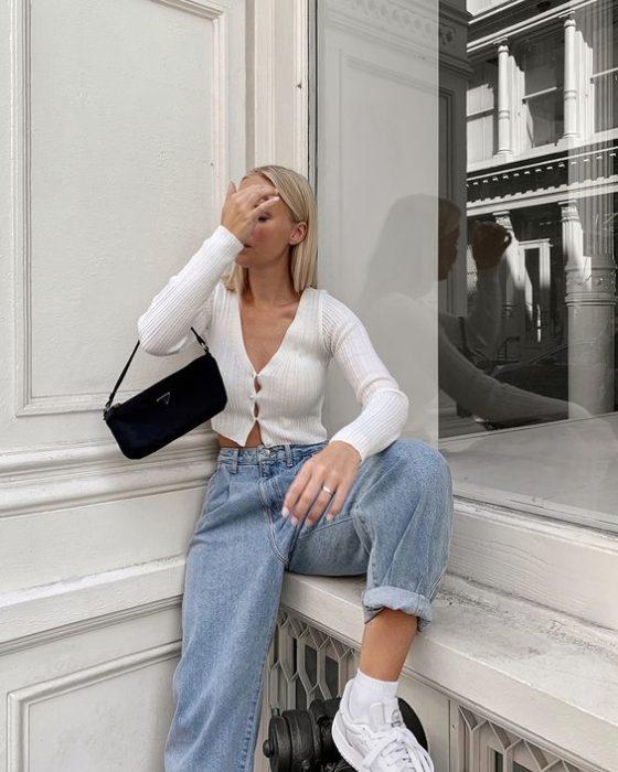 chica rubia con cárdigan blanco, bolso mini negro, slouchy jeans y tenis blancos