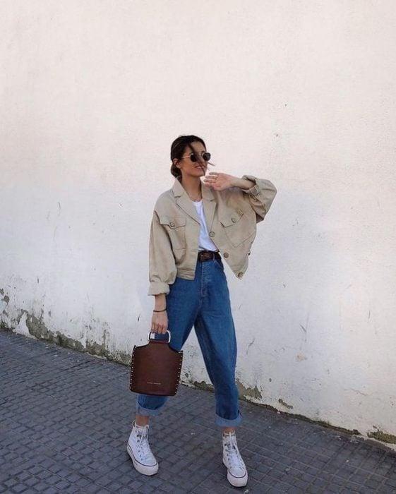chica de cabello castaño usando lentes de sol, cazadora beige, playera blanca, bolso cafe de piel, jeans slouchy y tenis deportivos blancos