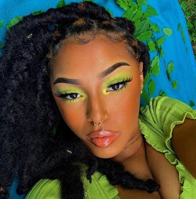 chica de complexion morena con maquillaje monocromatico de color verde, playera de color lima