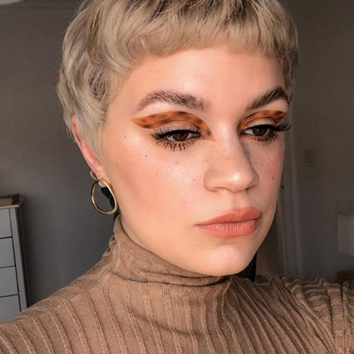 blonde girl with short hair with animal print makeup