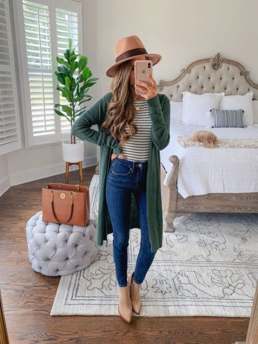 Woman takes selfie in front of the mirror with green cardigan and beige hat