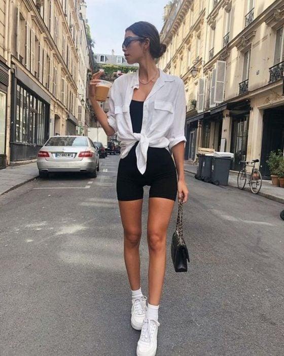 chica de cabello castaño usando biker shorts negros, top negro y camisa blanca encima, tenis deportivos blancos y bolso negro de mano